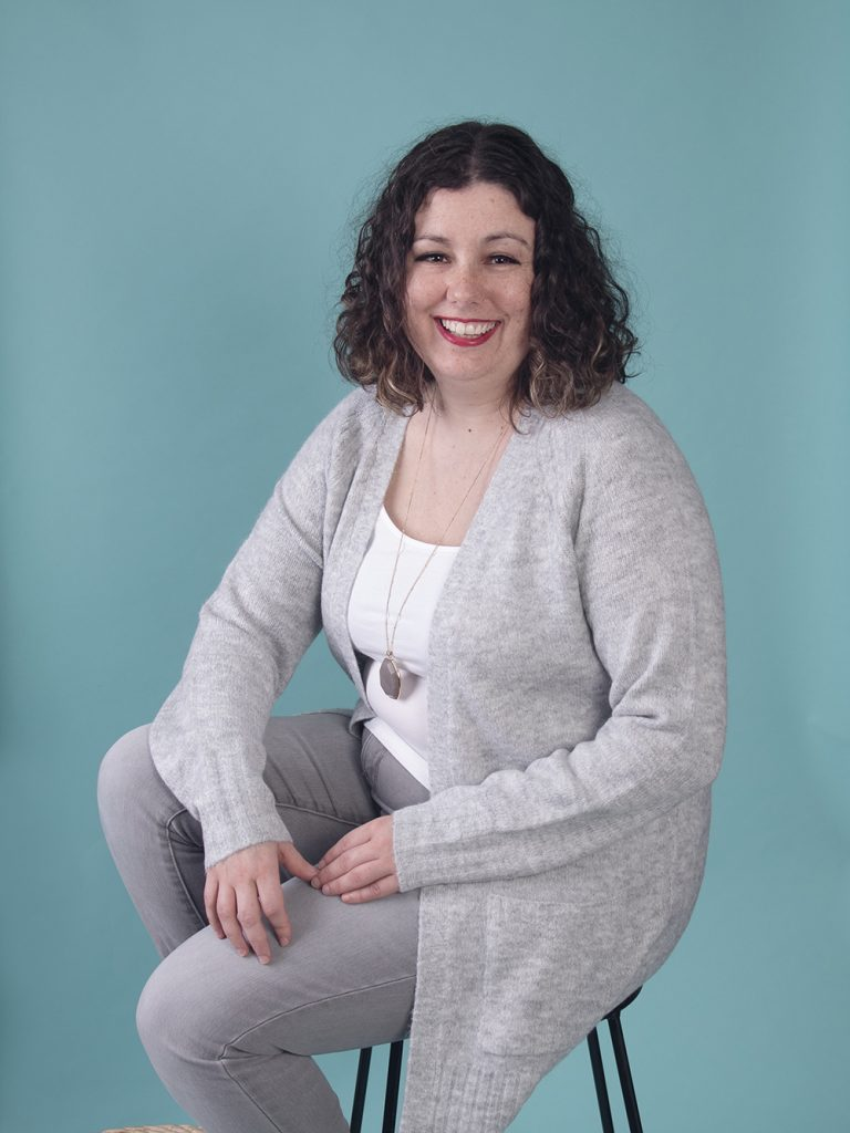 Female life coach dressed in grey sits on a stool in front of a blue backdrop and smiles.