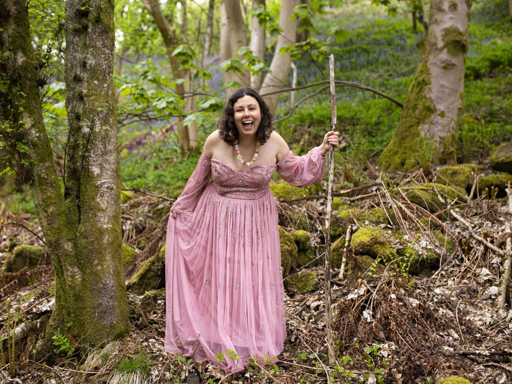 Woman in a pink gown holds a wooden staff and stands in the forest. Her mouth is open and smiling