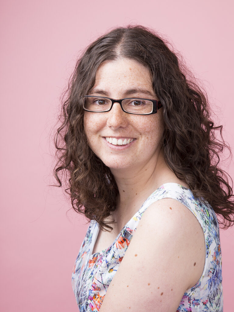 Headshot of a smiling woman wearing glasses and a flowery dress on a pink background