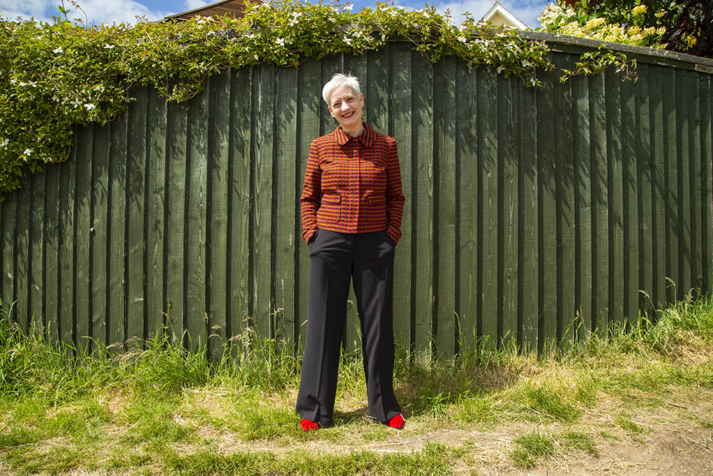 Professional woman in red blazer and black trousers with short white hair stands outside in the sunshine in front a green fence.