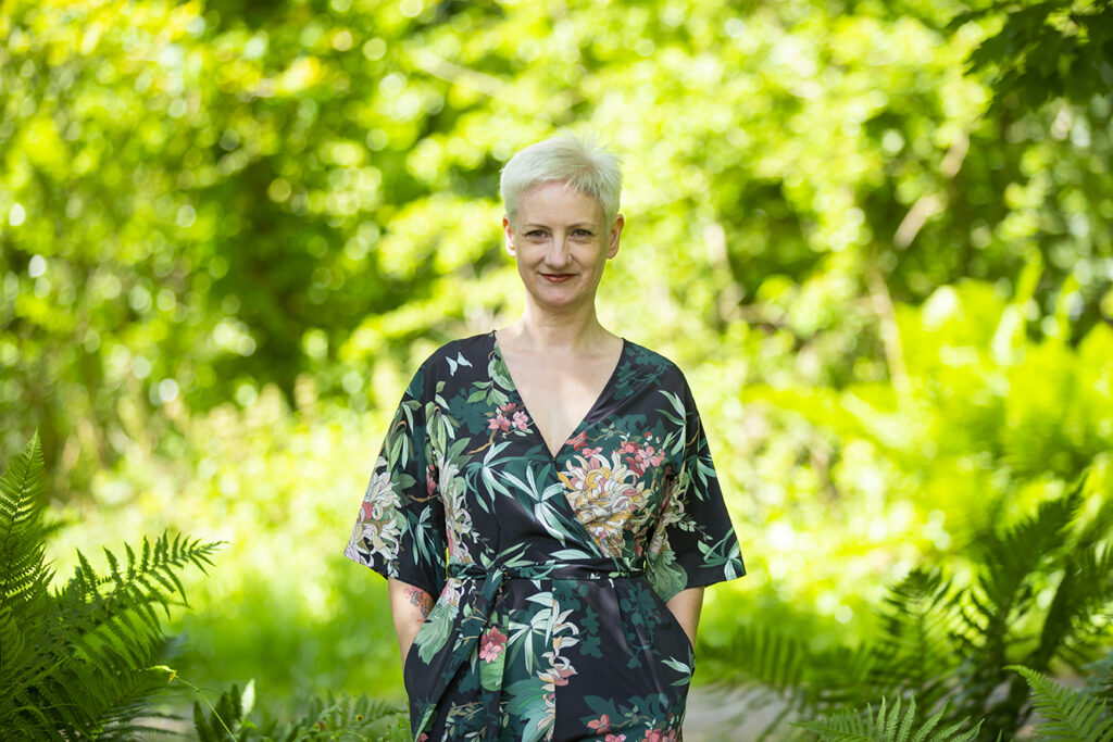 Woman with short, white hair wearing a floral jumpsuit stands outside in the woods smiling at the camera